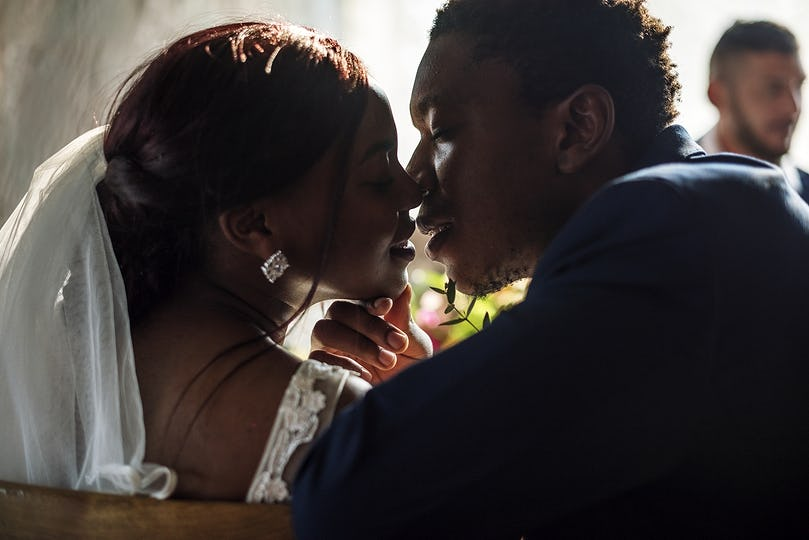 Newlywed African Descent Bride Kissing Groom Wedding Celebration