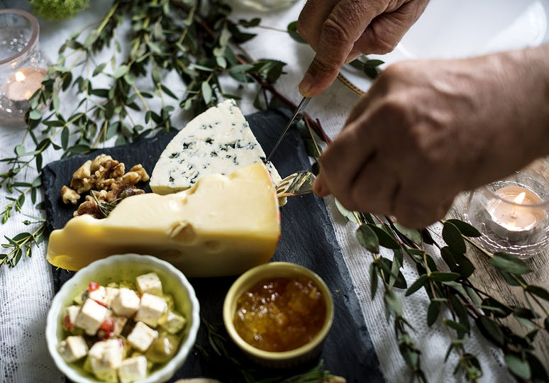 Close up of hands getting cheese on a plate