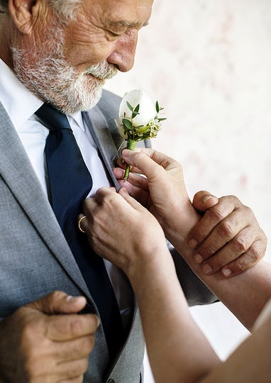 Hands Put on Small Flower Bouquet on Tuxedo