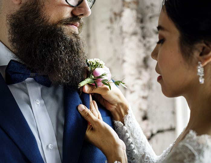 Bride Put on Small Flower Bouqet on Groom Tuxedo