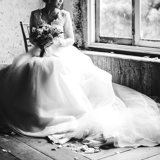 Bride in her gown with a bouquet of flowers sitting by the window