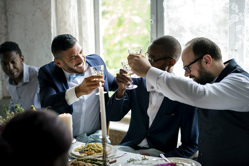 People holding their champagne glasses for a toast at a wedding table