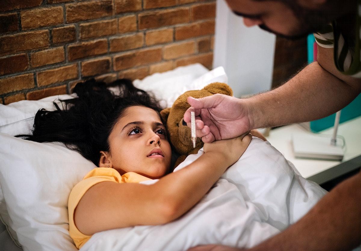 Dad taking sick daughter's temperature