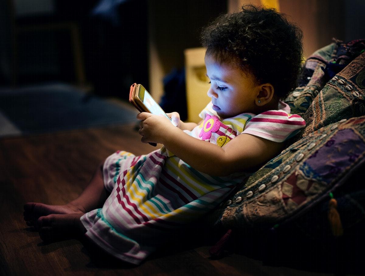 Little toddler girl using mobile phone