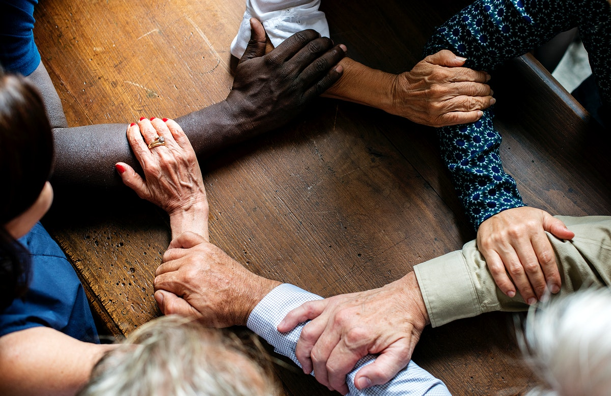 Group of diverse hands holding each other forearms