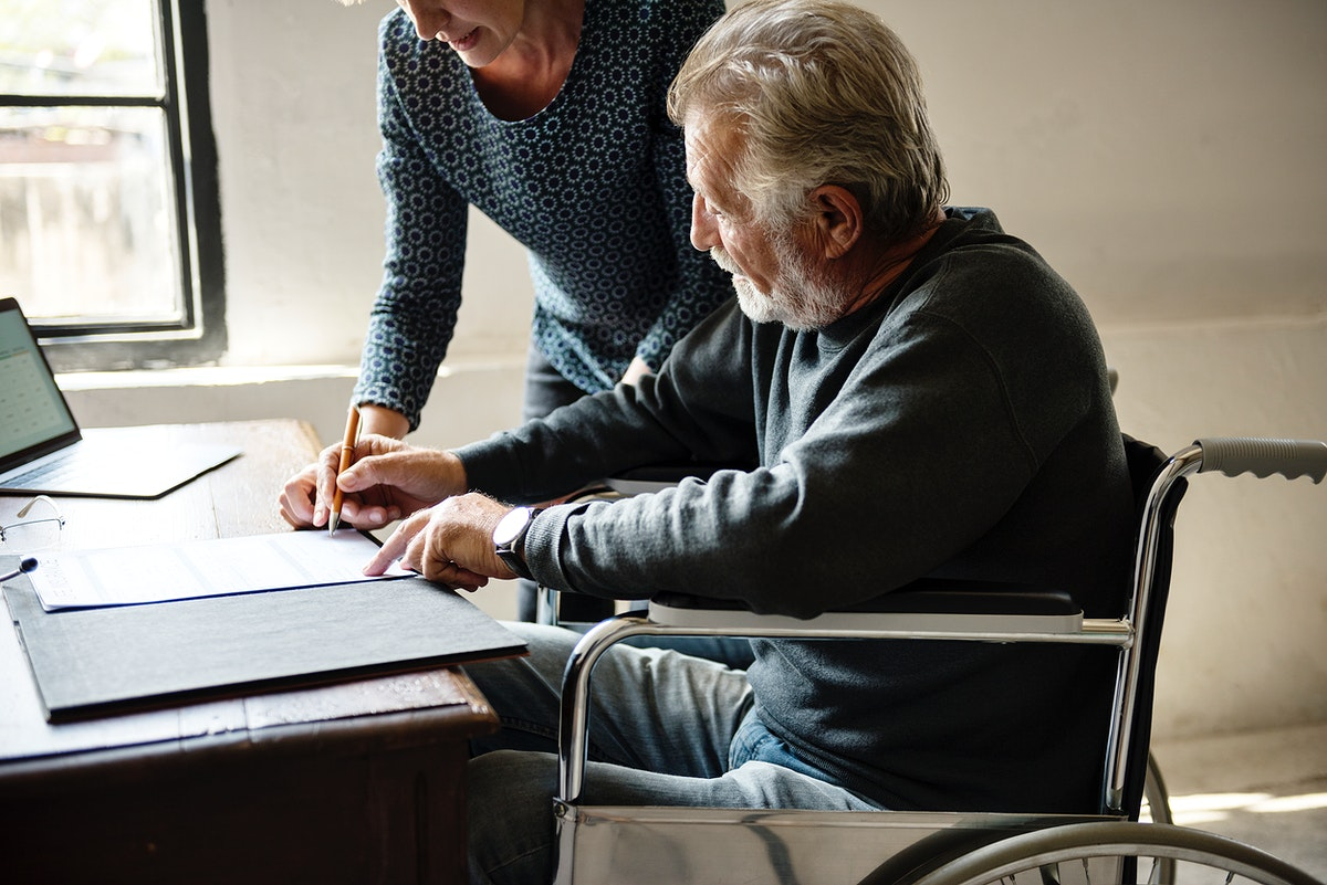 Side view of elderly man completing documents