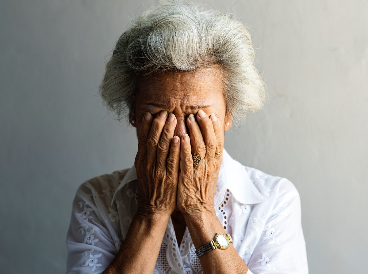 Elderly Asian woman with hands covered her face