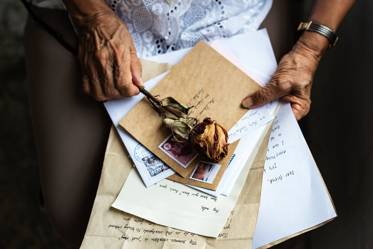 Elderly woman holding old letters and dried rose