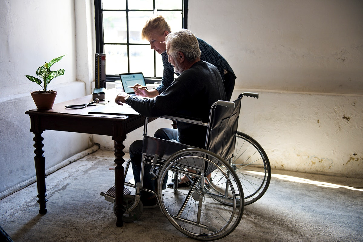 Side view of elderly man sitting on wheelchair looking at documentation