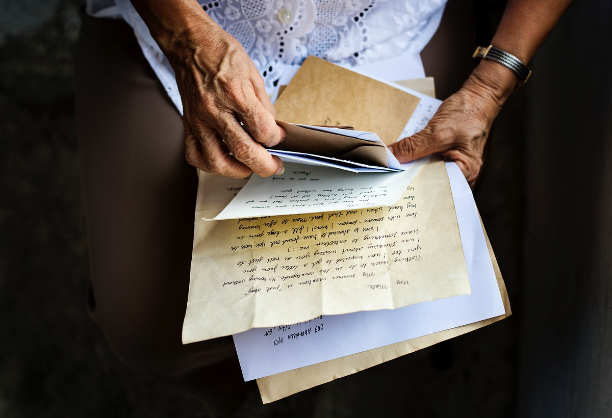 Elderly woman holding old letters in her hands