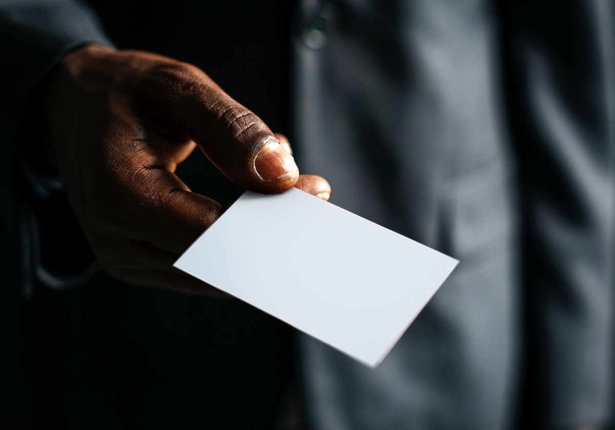 Closeup of hand holding blank white paper card