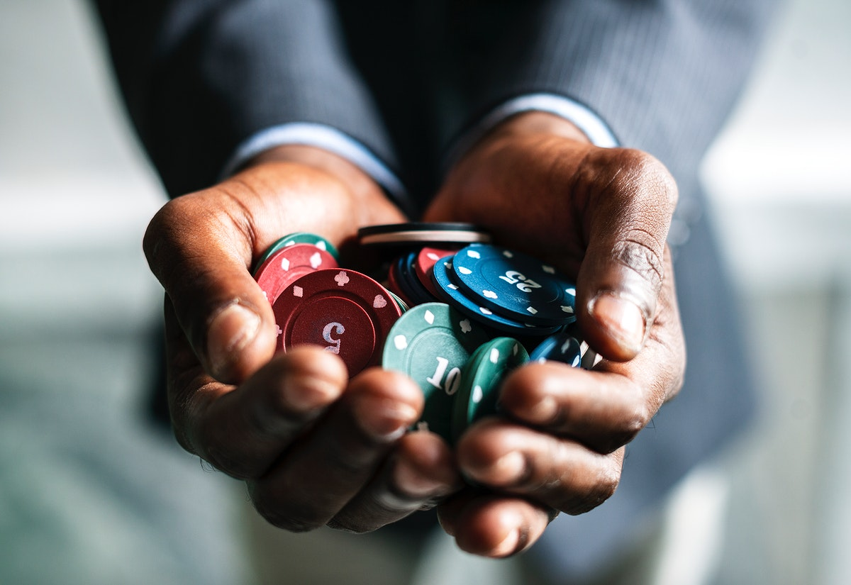 Man holding a handful of gambling chips
