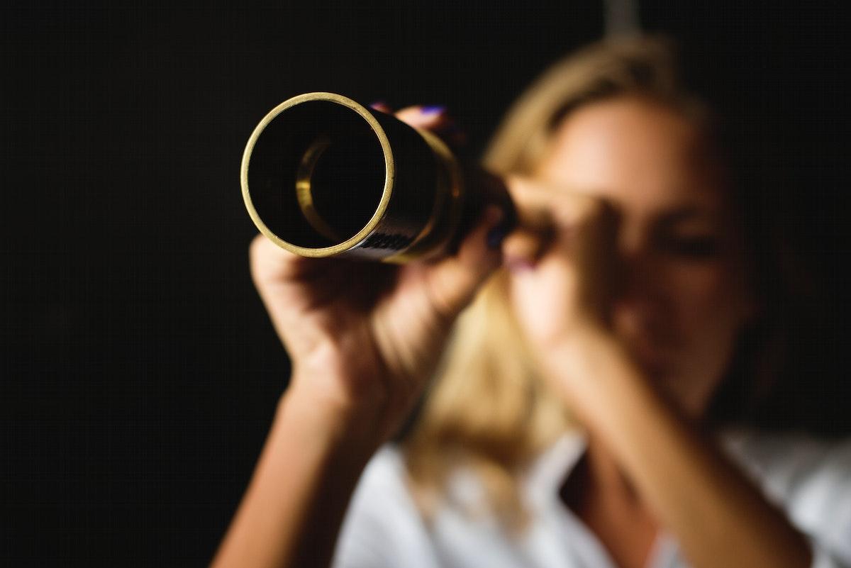 Caucasian woman using telescope spyglass