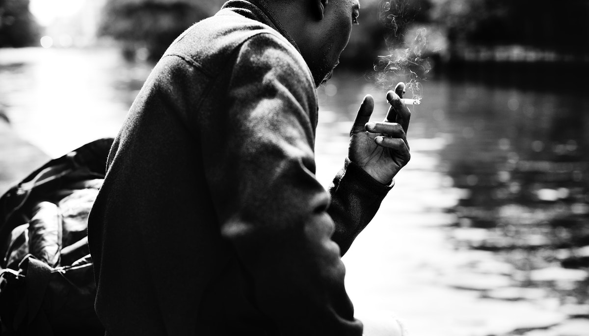 Man smoking a cigarette by the water