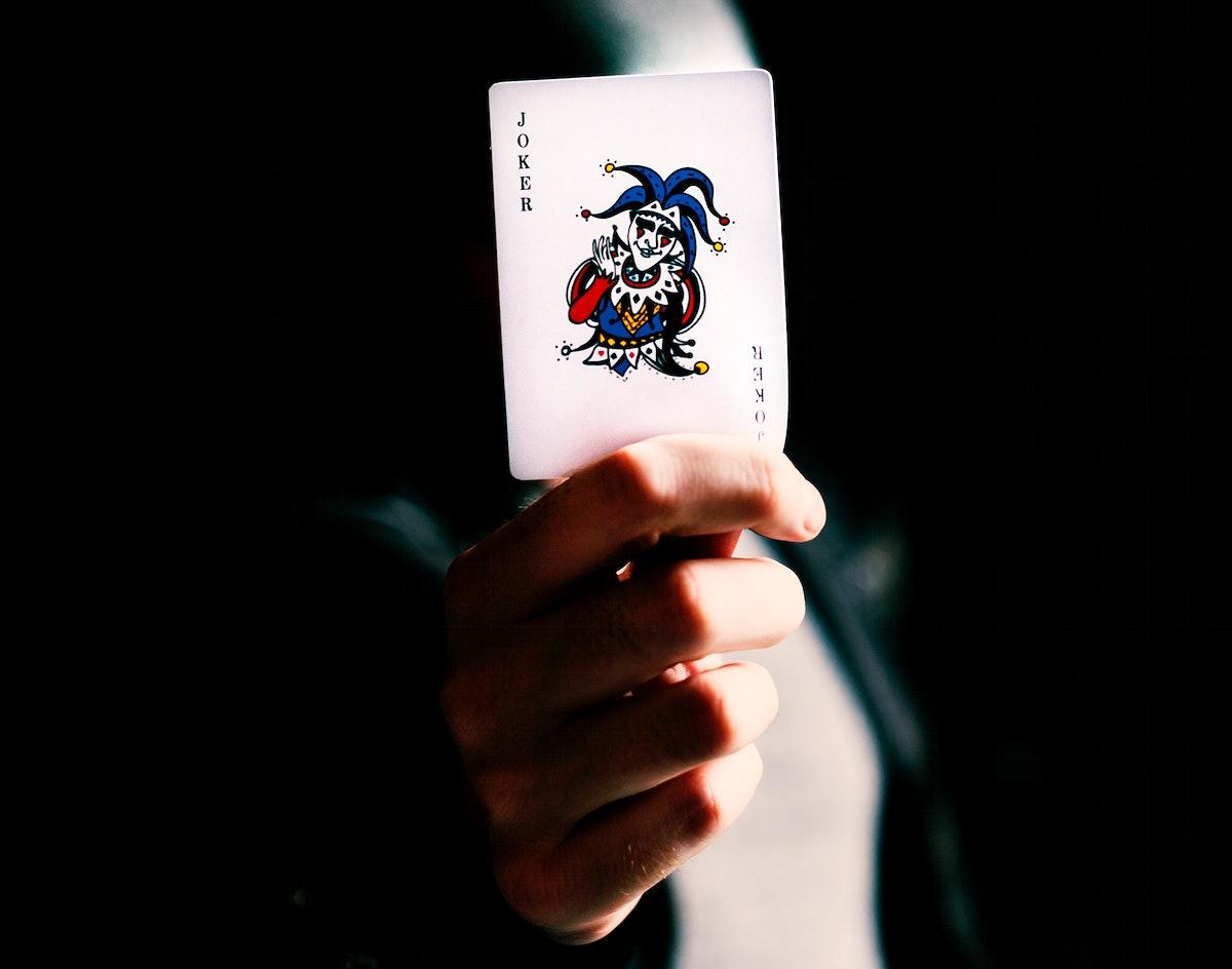 Male card dealer holding a joker card