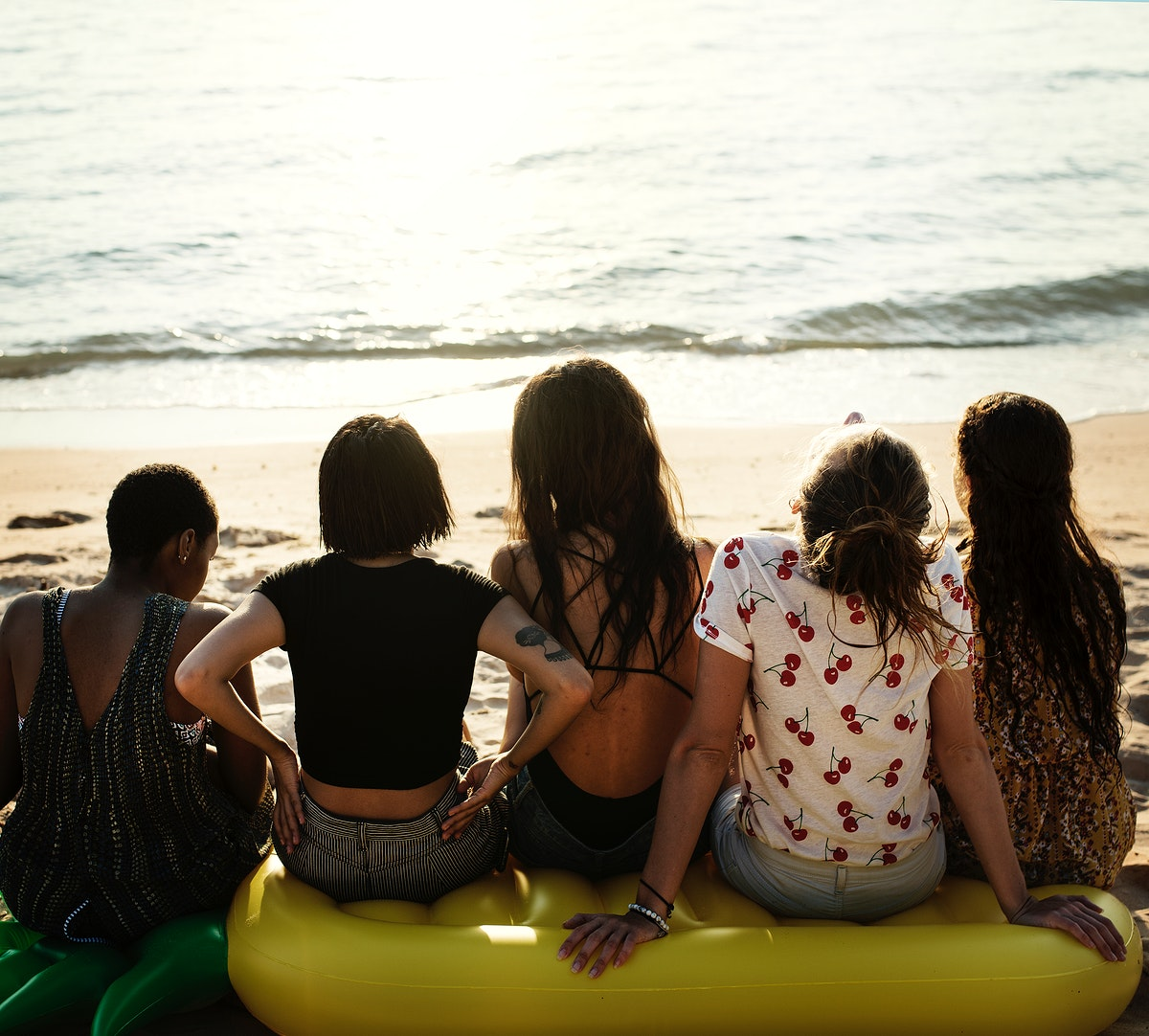 A diverse group of woman friends sitting at the beach together
