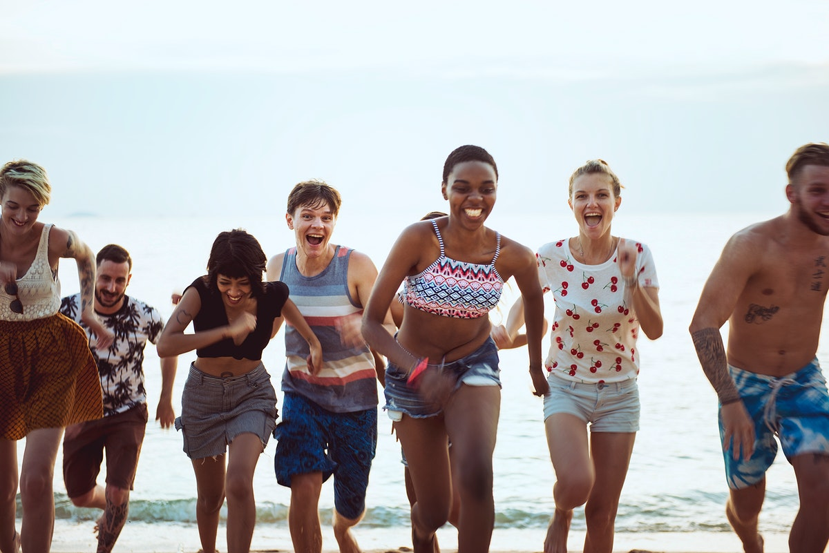 A diverse group of friends running at the beach together