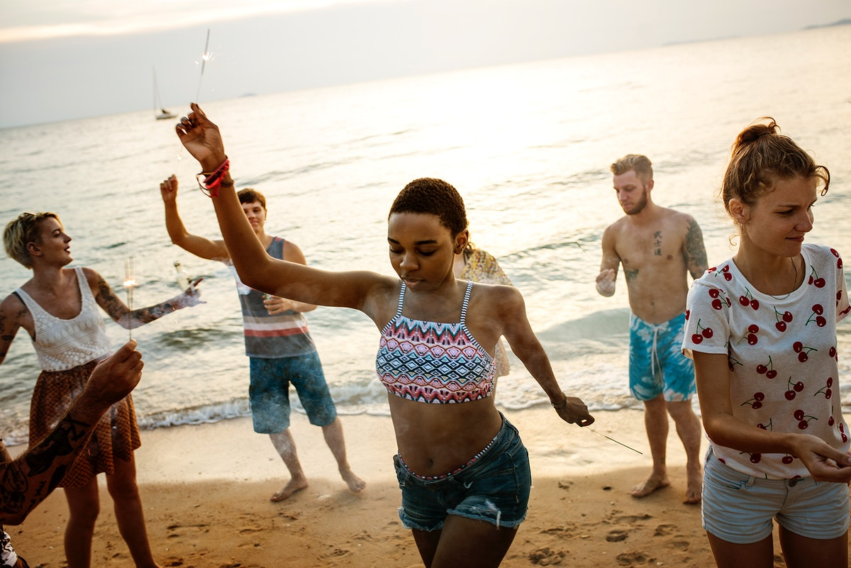 Group of diverse friends enjoying sparklers at the beach together