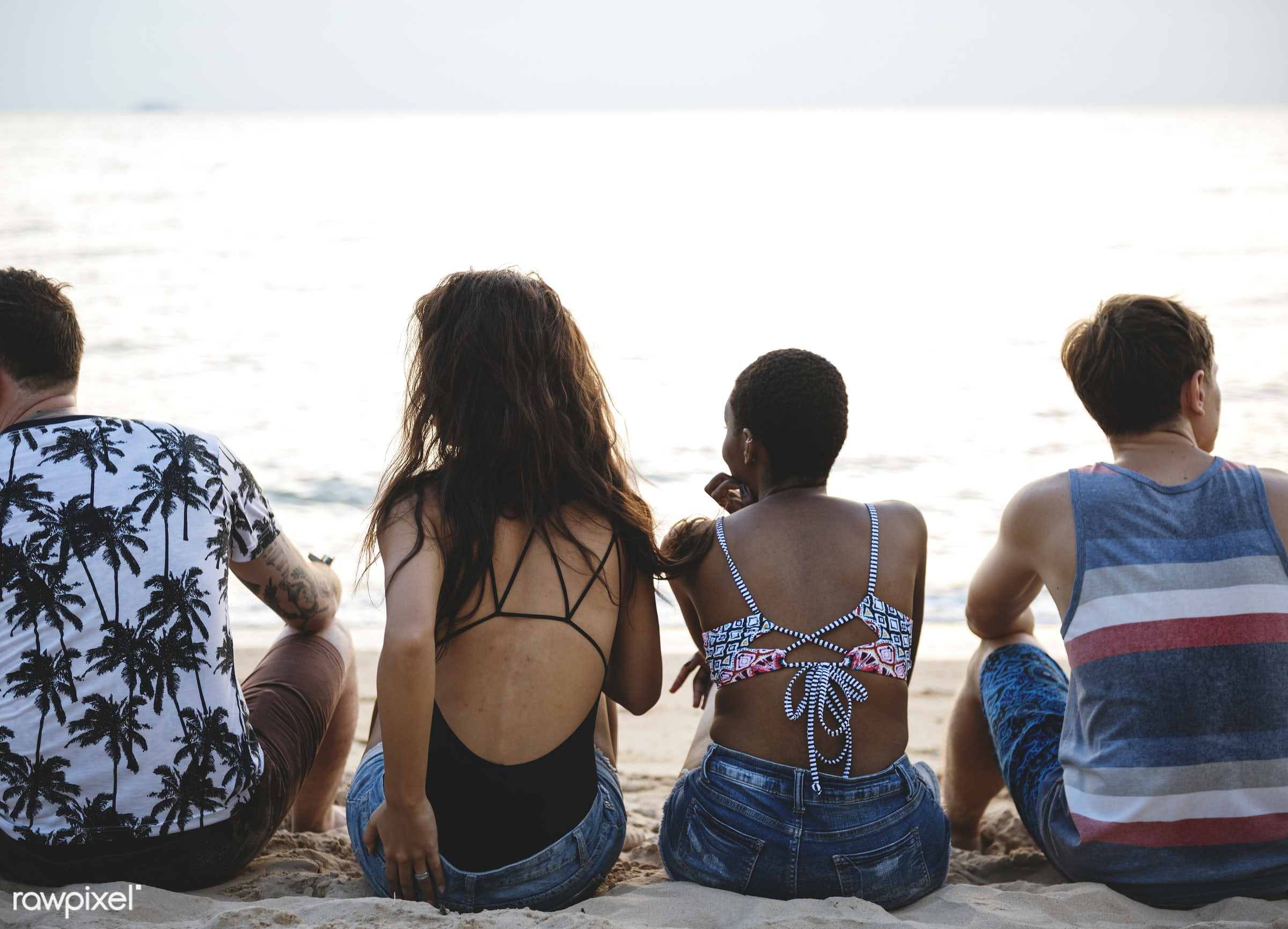 A diverse group of friends sitting at the beach together - relax, diverse, beach, recreation, people, together, coast, break...