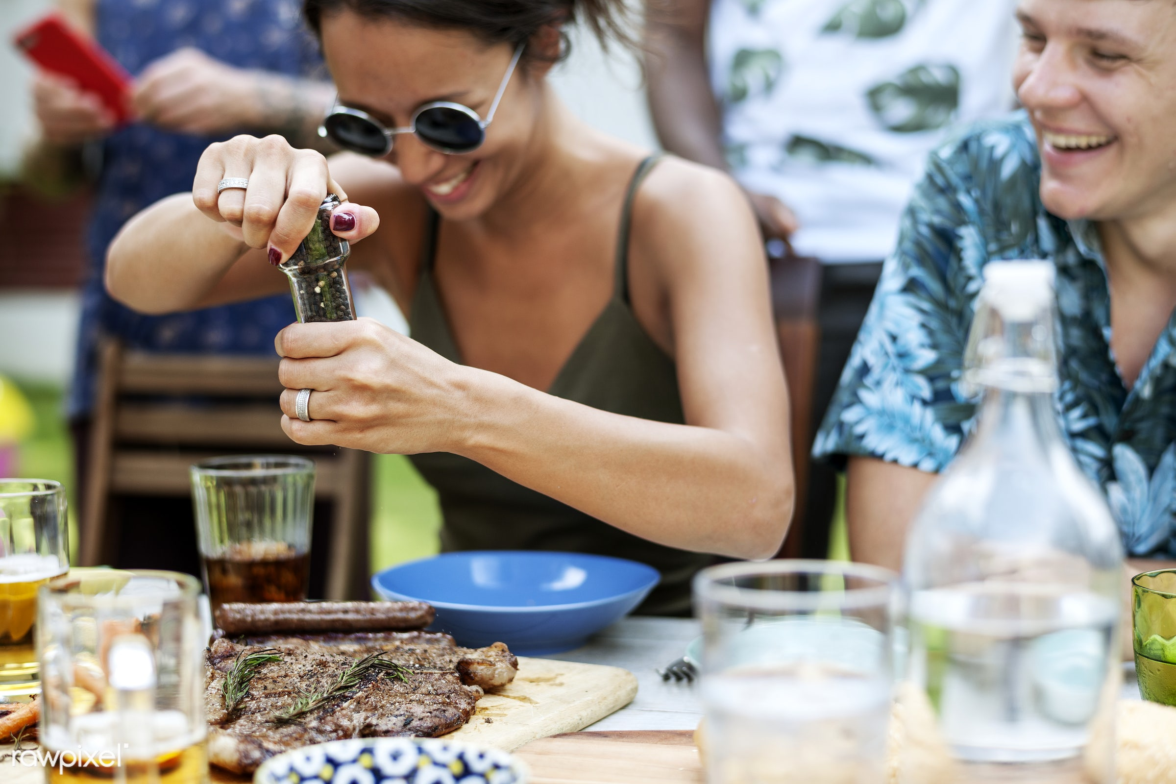 A woman using a pepper grinder at a meal - peppers, yard, cuisine, relax, diverse, party, homemade, spices, people, together...