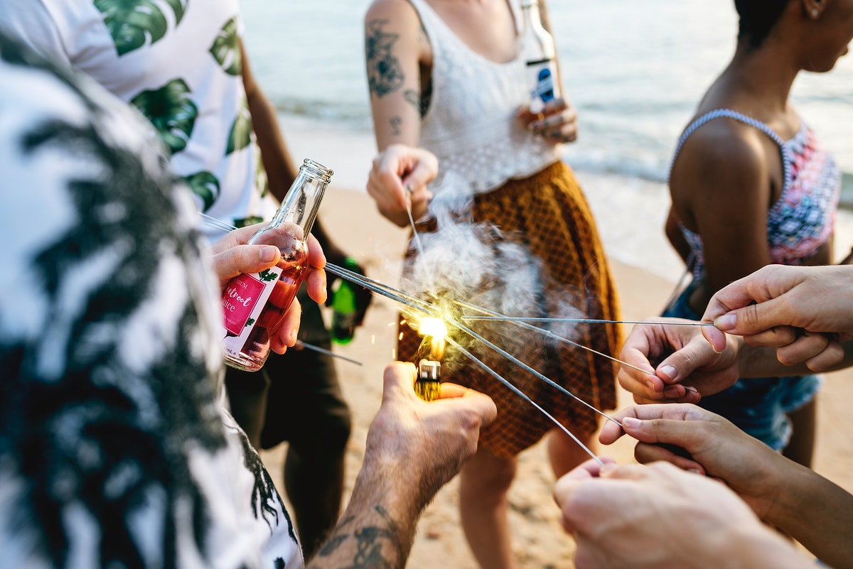A diverse group of friends enjoying sparklers at the beach together