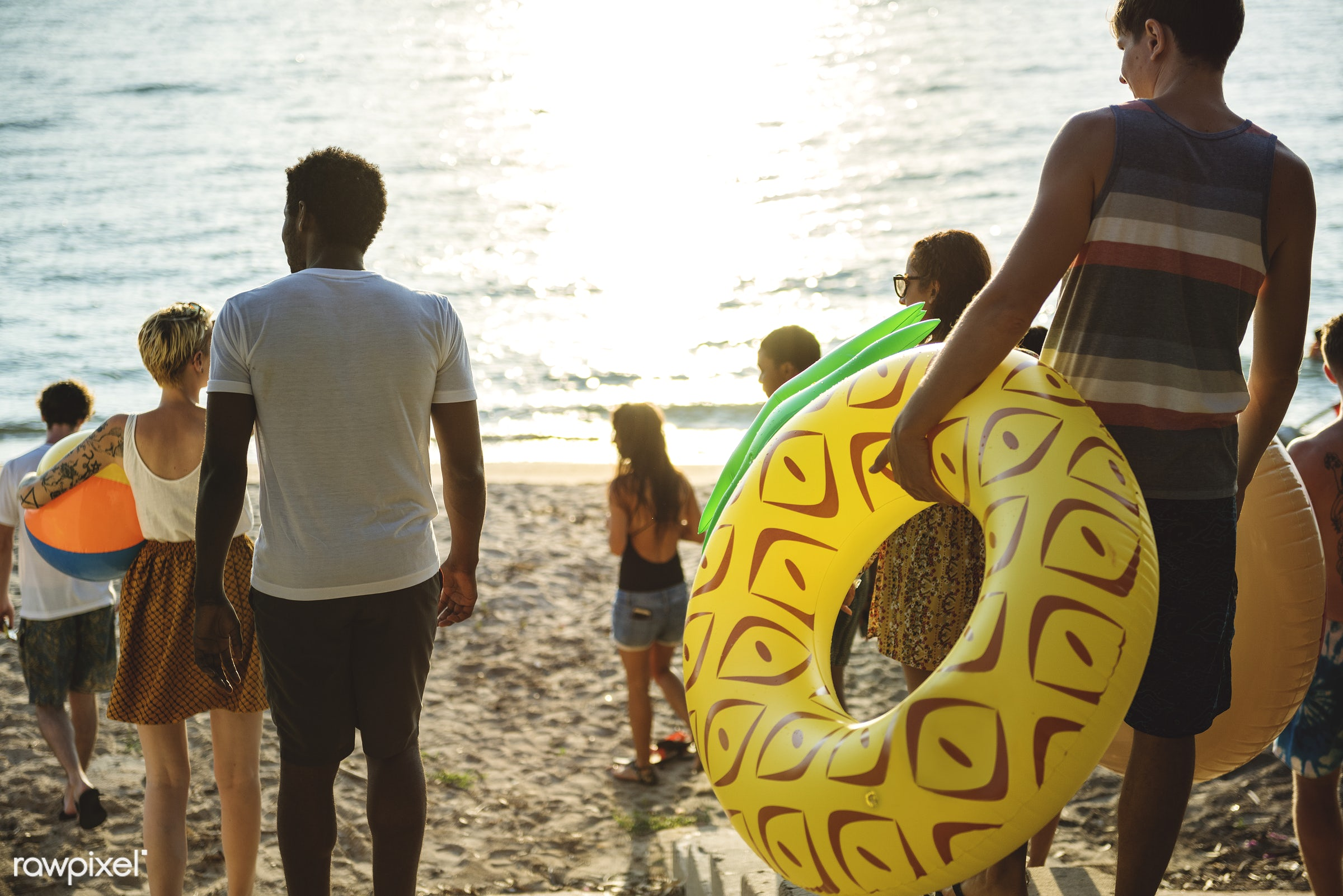 A diverse group of friends walking down to the beach with inflatable tubes - walking, relax, diverse, beach, recreation,...