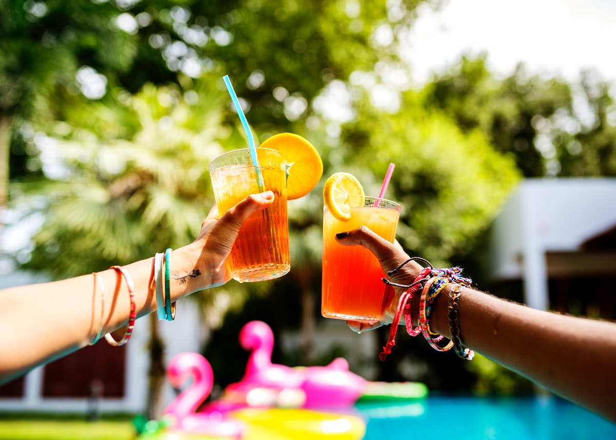 Hands toasting juice glasses by the pool summer time