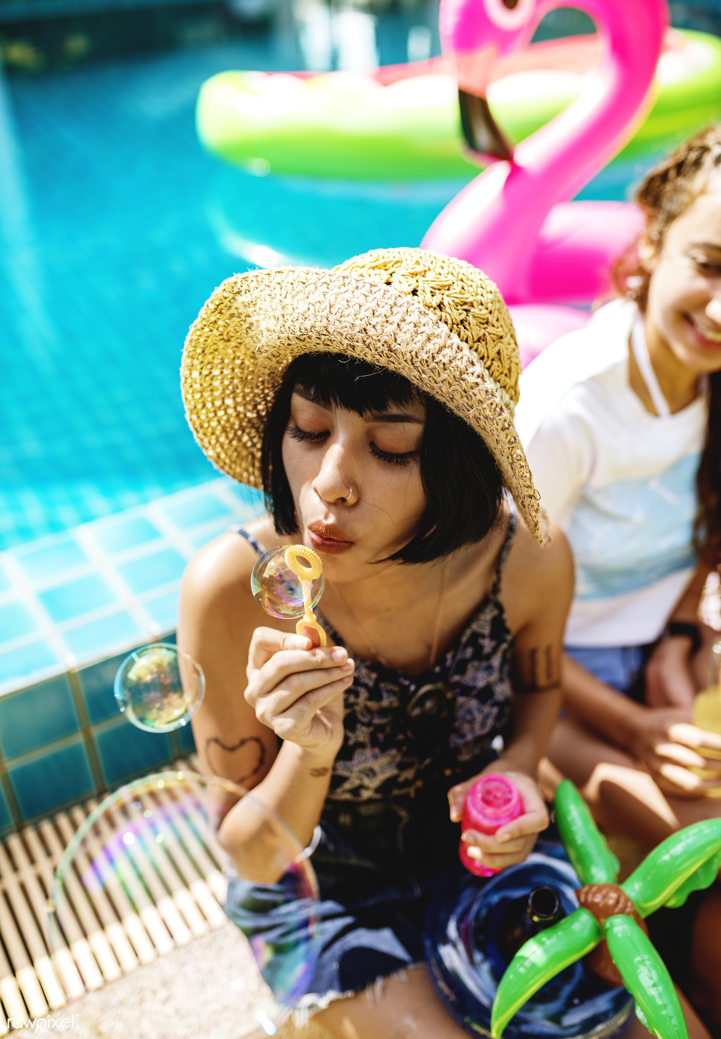 A diverse group of female friends enjoying summer time by the pool and playing with a soap bubbler - relax, diverse,...