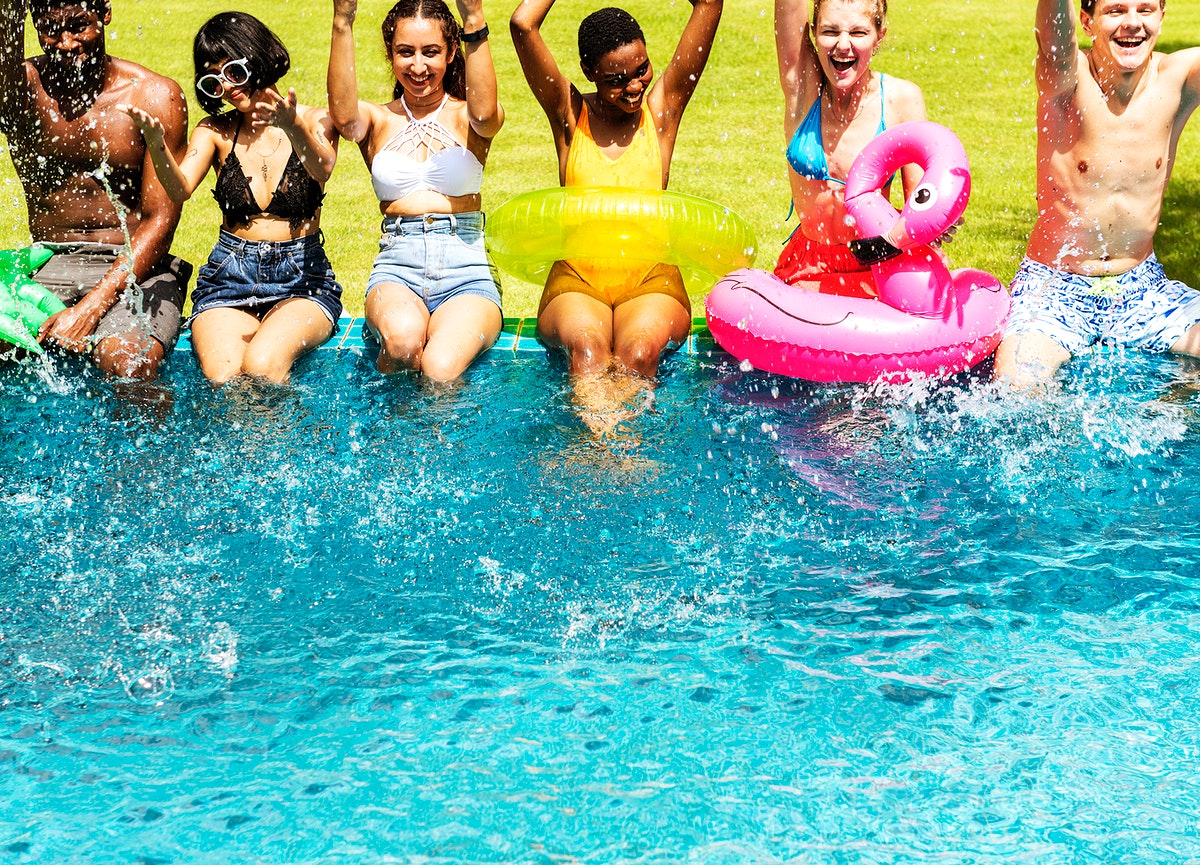 A diverse group of friends enjoying summer time by the pool with inflatable floats