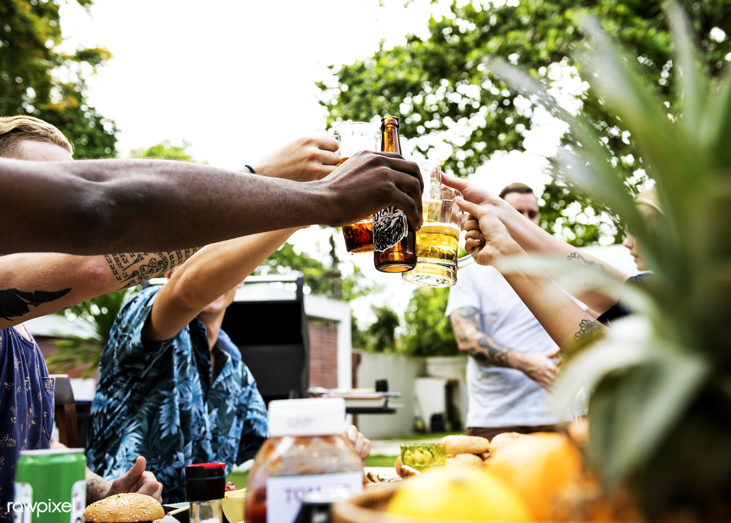 A diverse group of friends celebrating and drinking beers together in the summer time - activity, alcohol, beers, beverage,...