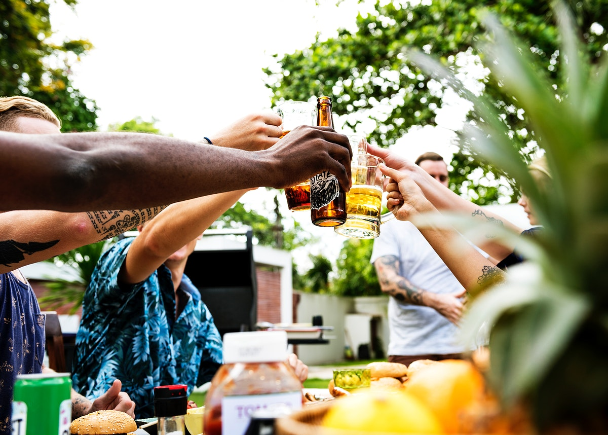A diverse group of friends celebrating and drinking beers together in the summer time