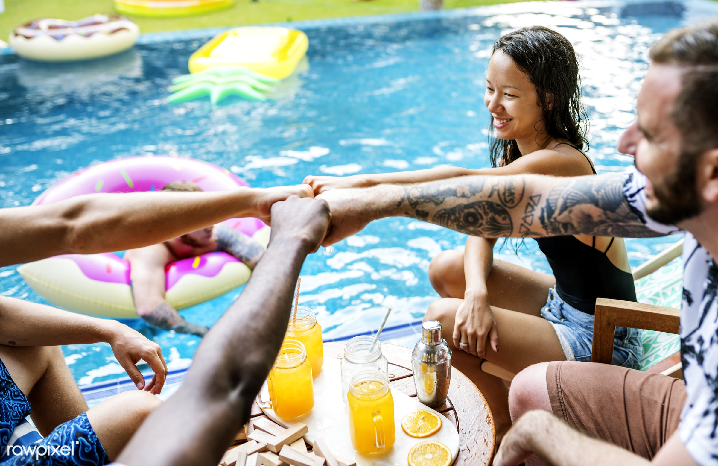 A diverse group of friends enjoying summer time by the pool - hands out, relax, diverse, recreation, party, people, together...