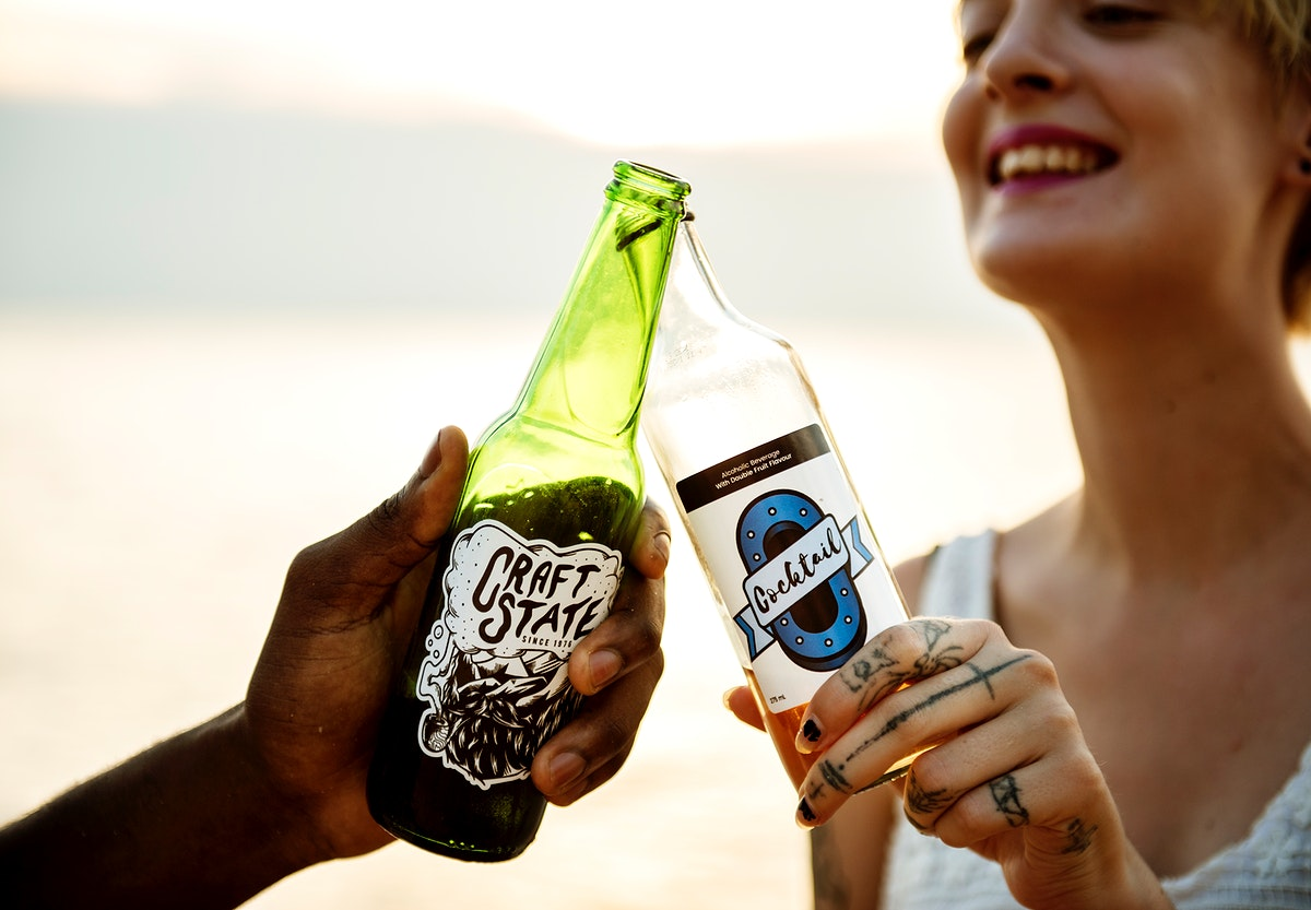 Clsoeup of caucasian woman clinking beer bottle with black man at the beach