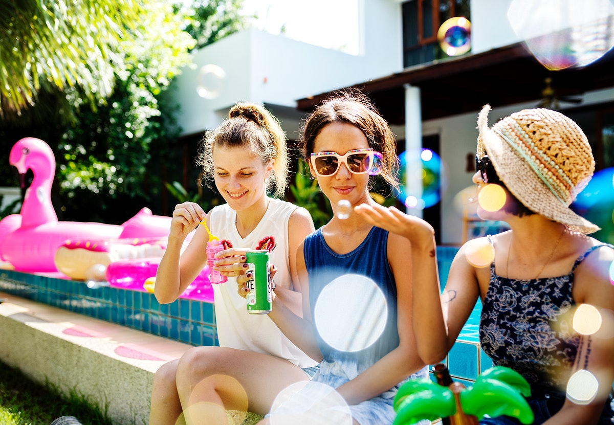 A diverse group of female friends enjoying summer time by the pool and playing with a soap bubbler