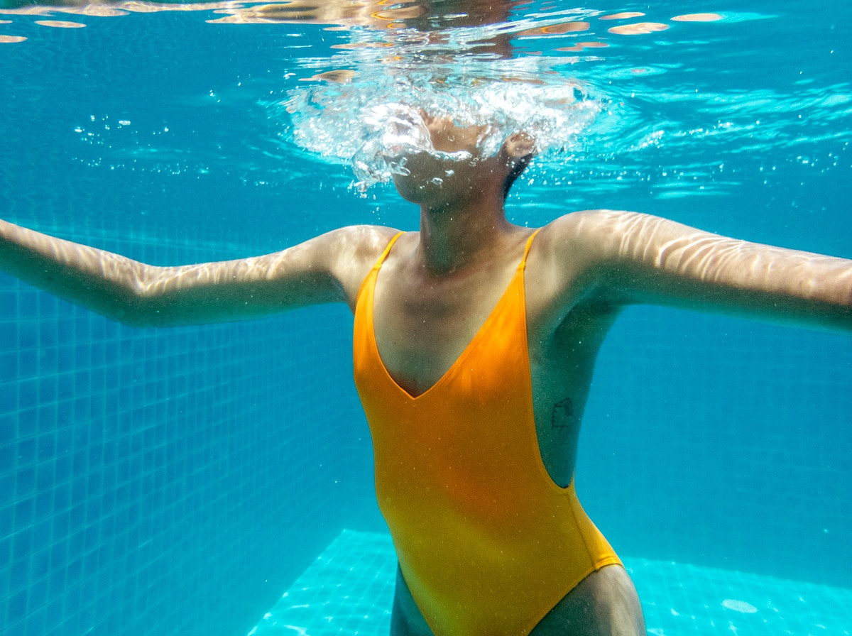 African descent woman underwater in swimming pool