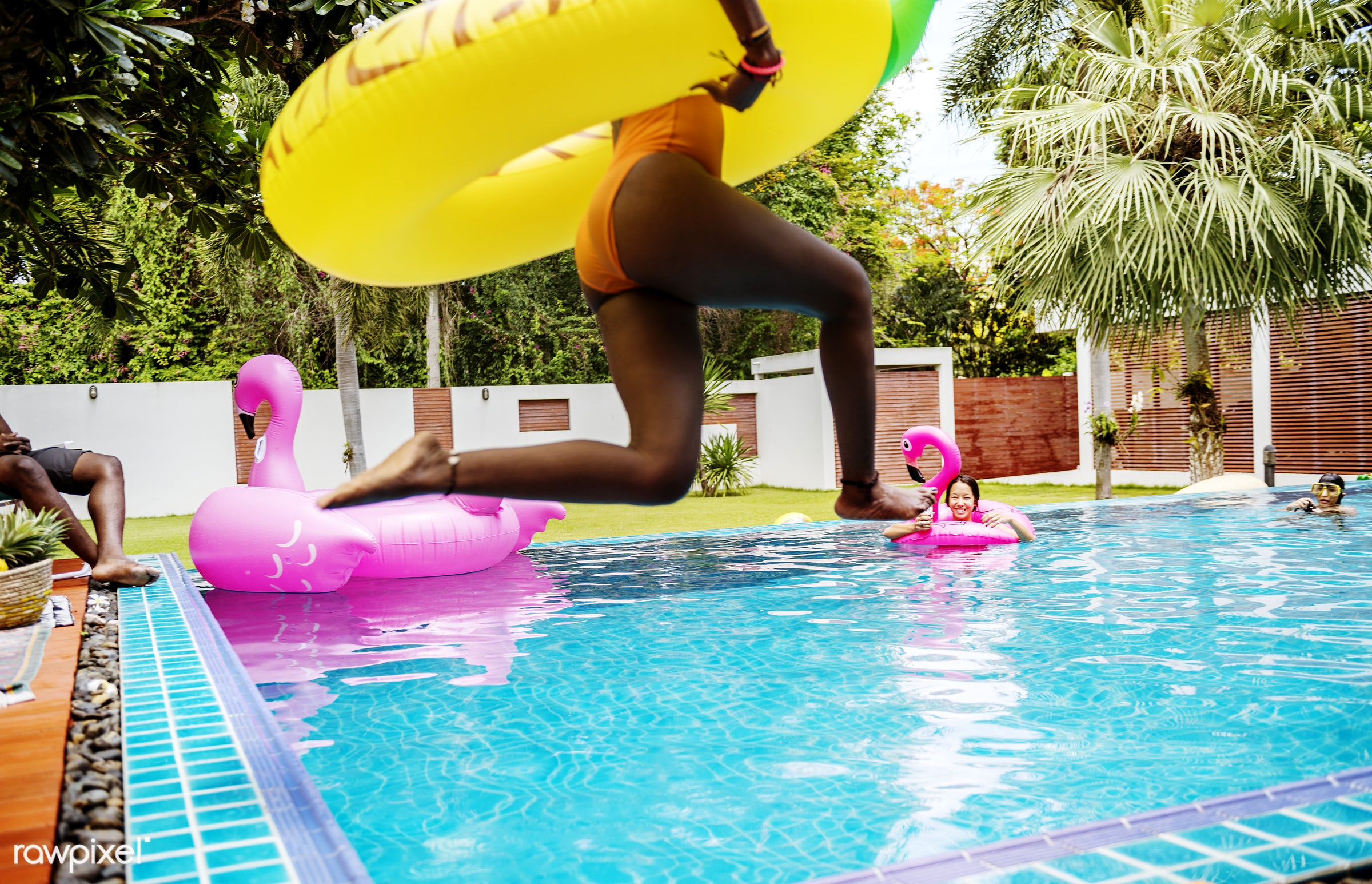 An African woman jumping into the pool with inflatable float and enjoying summer time - pool, african descent, cheerful,...