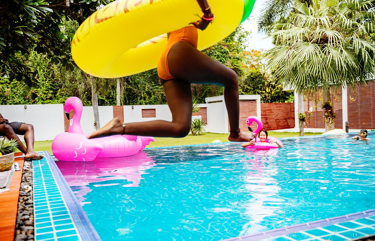 An African woman jumping into the pool with inflatable float and enjoying summer time