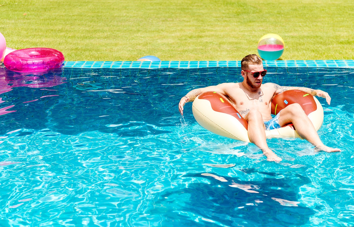 A Caucasian tattooed man on an inflatable float in the swimming pool