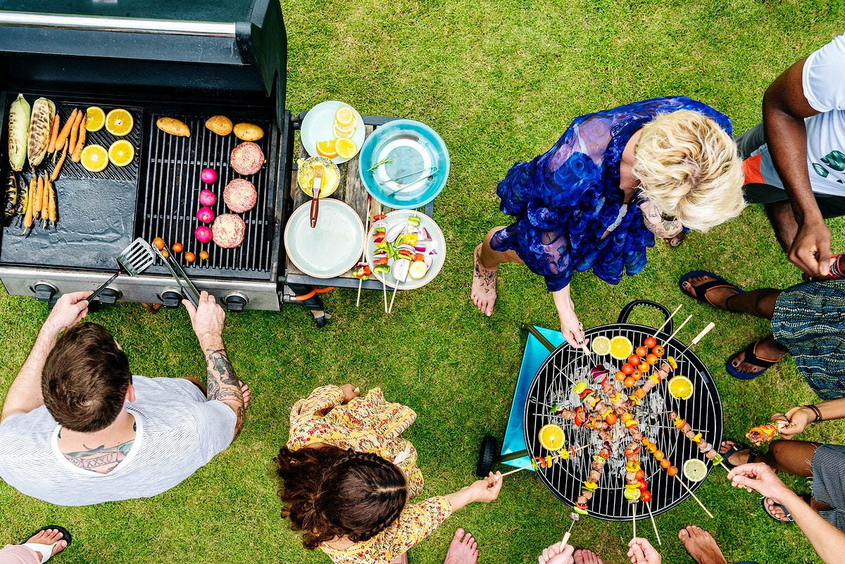 Group of diverse friends grilling barbecue outdoors