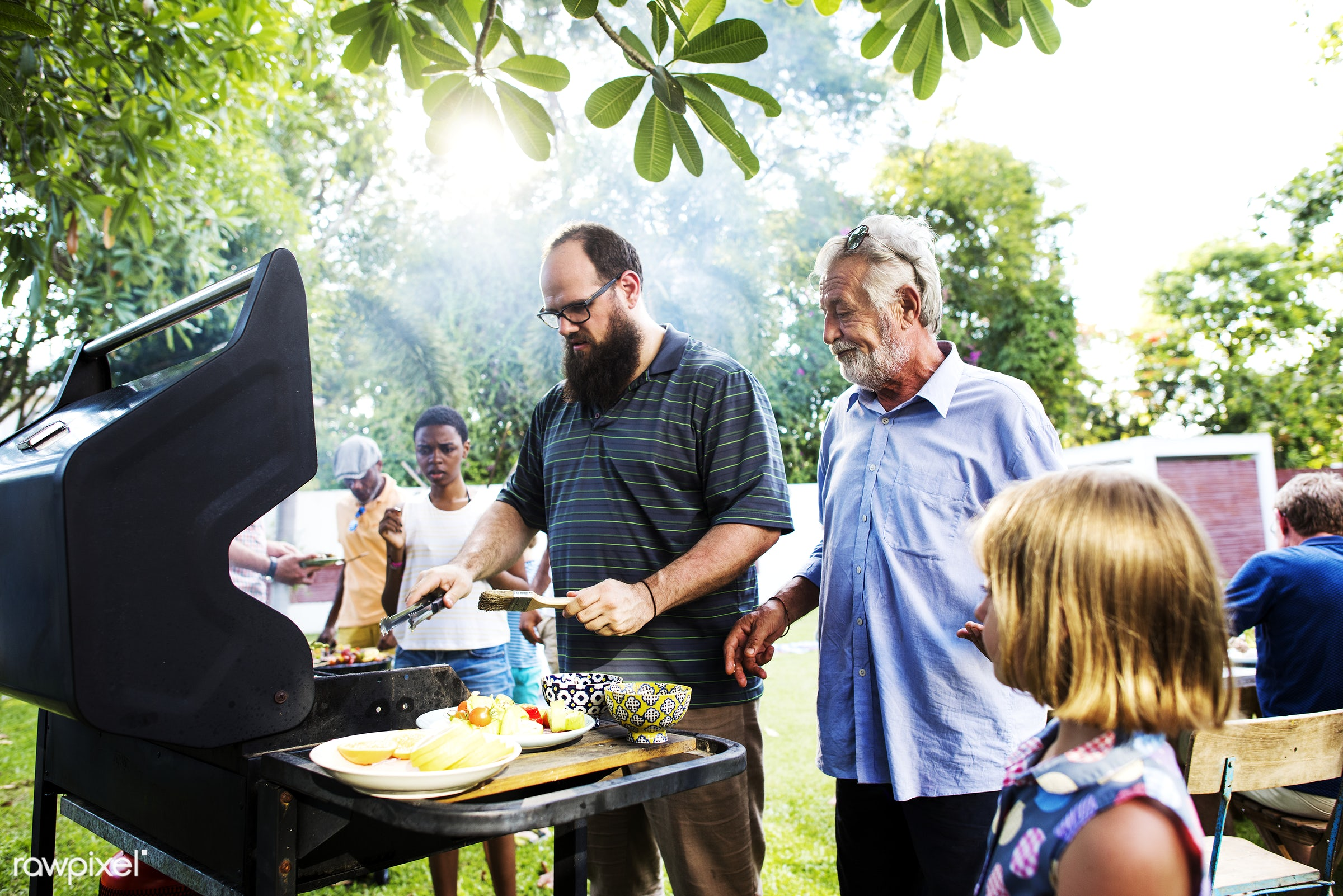 Diverse people enjoying barbecue party together - barbecue, family, cooking, backyard, bbq, cook, cookout, diverse, food,...