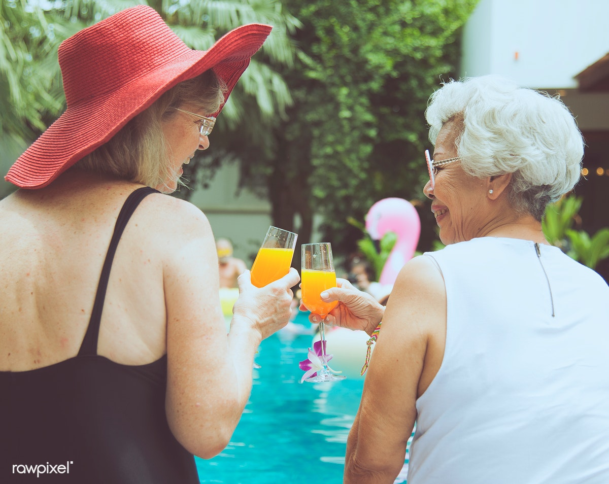 a5ed82c21b61a Senior couple women with orange juice by the pool together