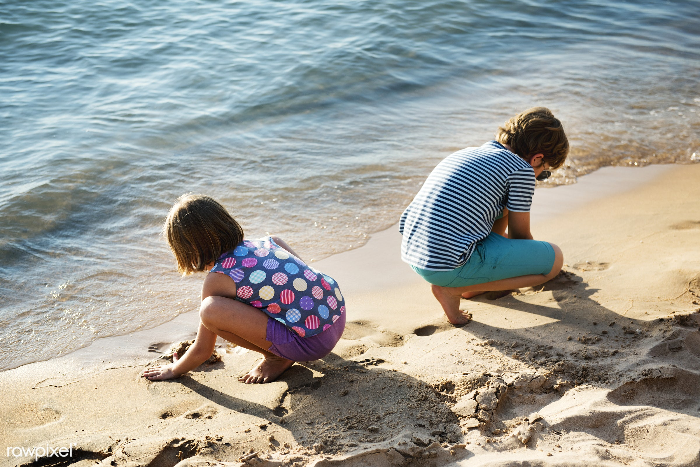 Closeup of caucasian kids playing with the sand together at the beach - beach, brother, cheerful, children, closeup, coast,...