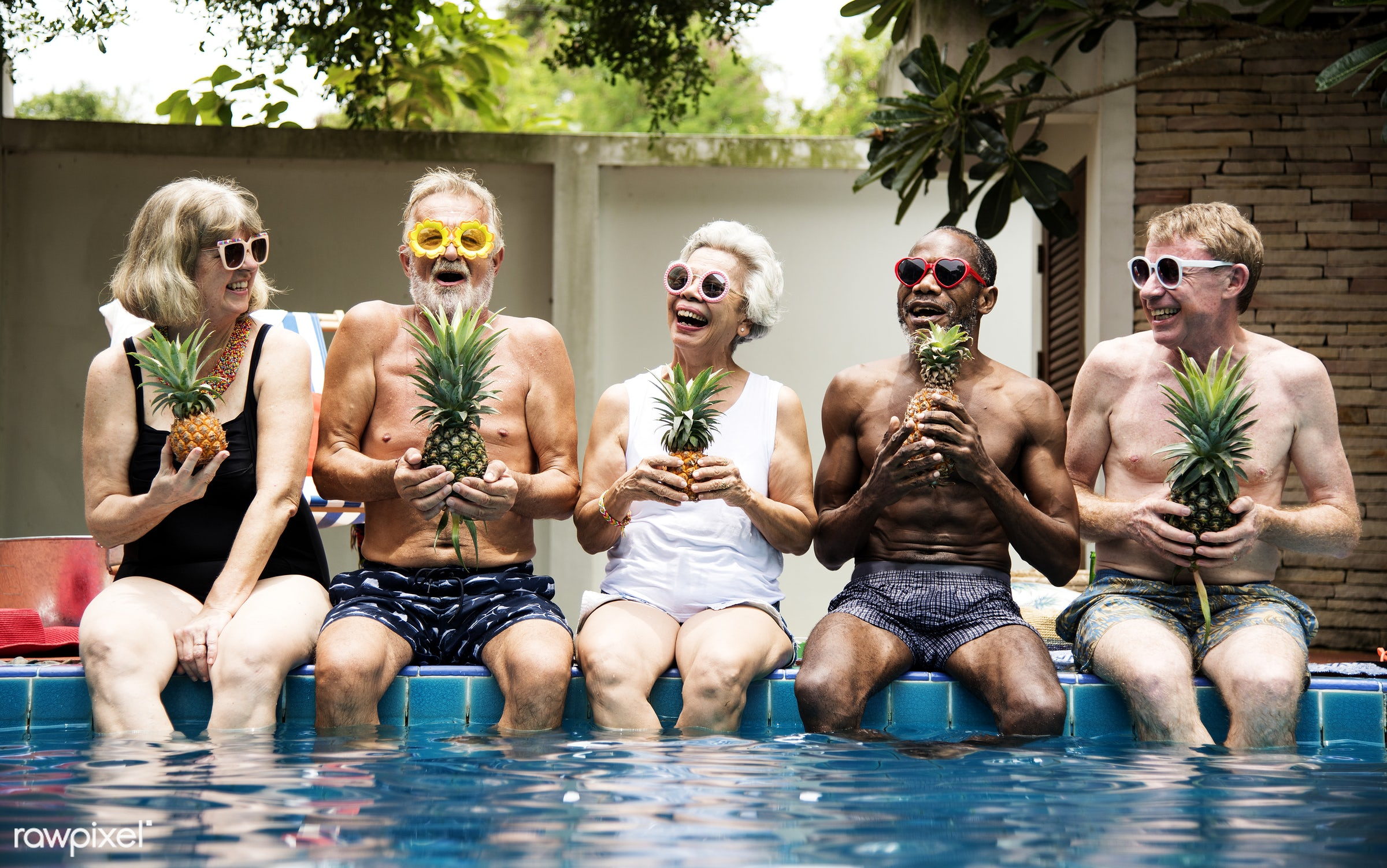 Group of diverse senior adults sitting at poolside holding pineapples together - happy, cheerful, diverse, enjoy, enjoying,...