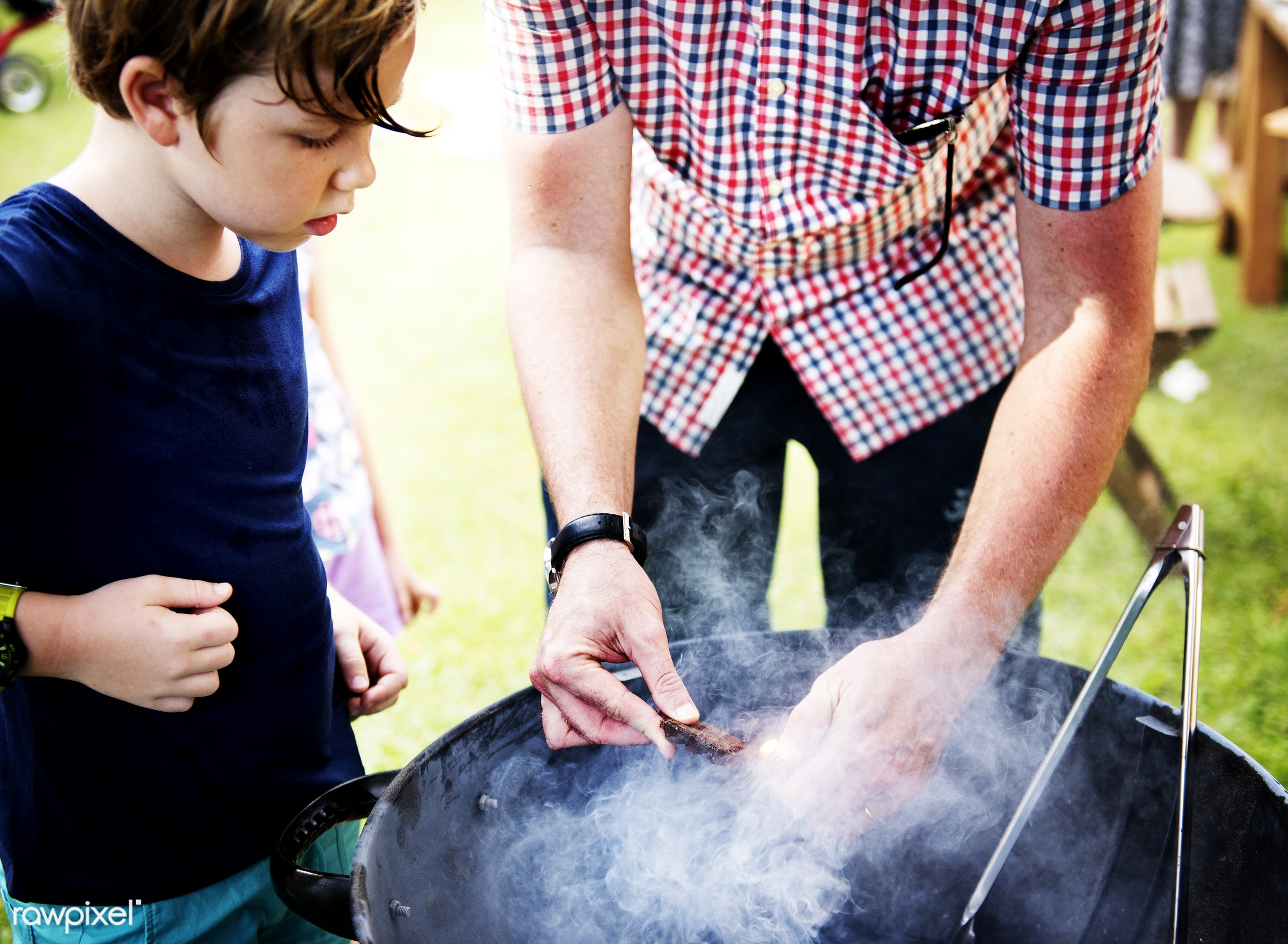 Closeup of father preparing charcoal grill for barbecue party with son - barbecue, activity, backyard, boy, charcoal, child...