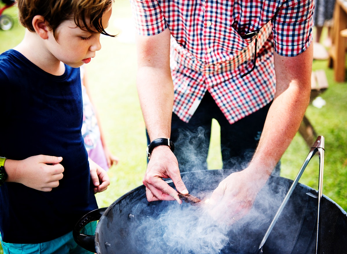 Closeup of father preparing charcoal grill for barbecue party with son