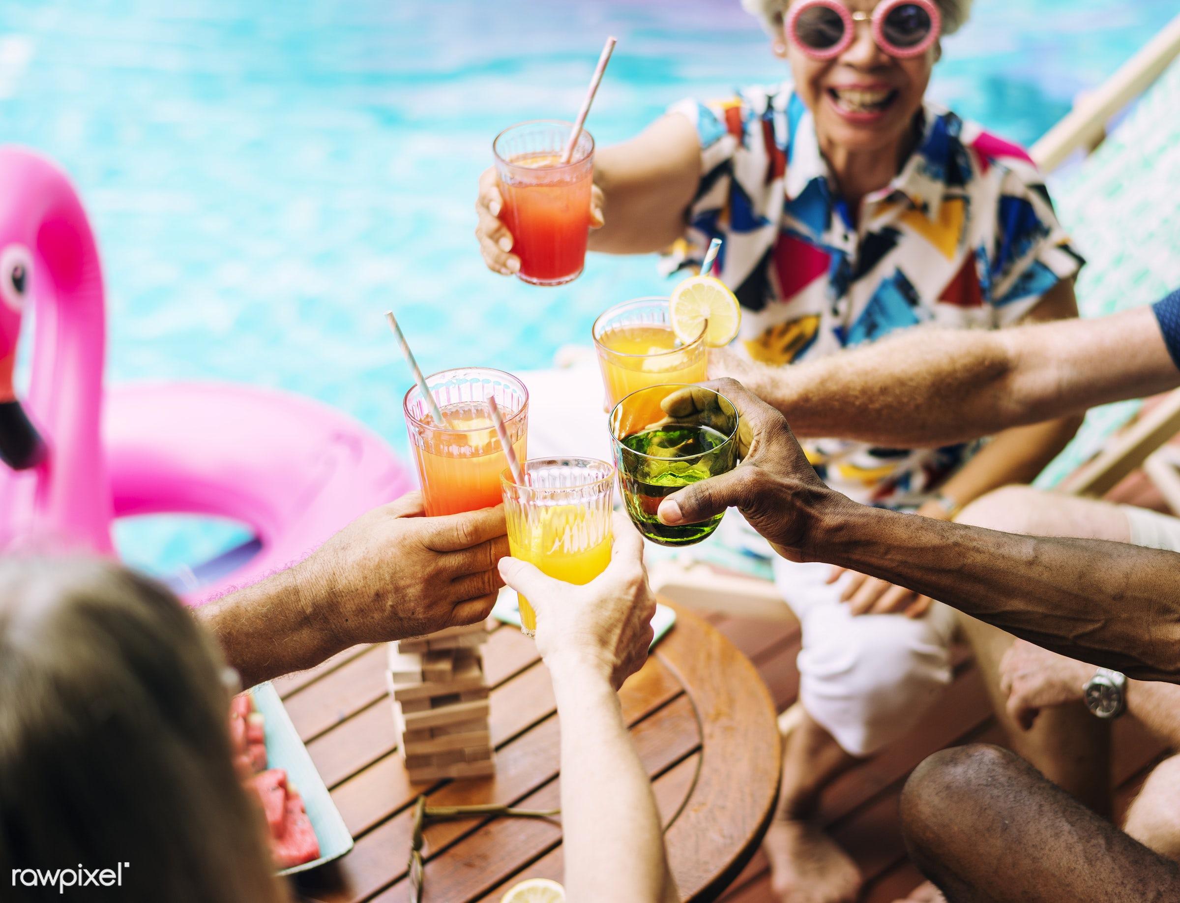 Group of diverse senior adult enjoying beverage by the pool together - beverage, closeup, diverse, drinks, enjoy, enjoyment...