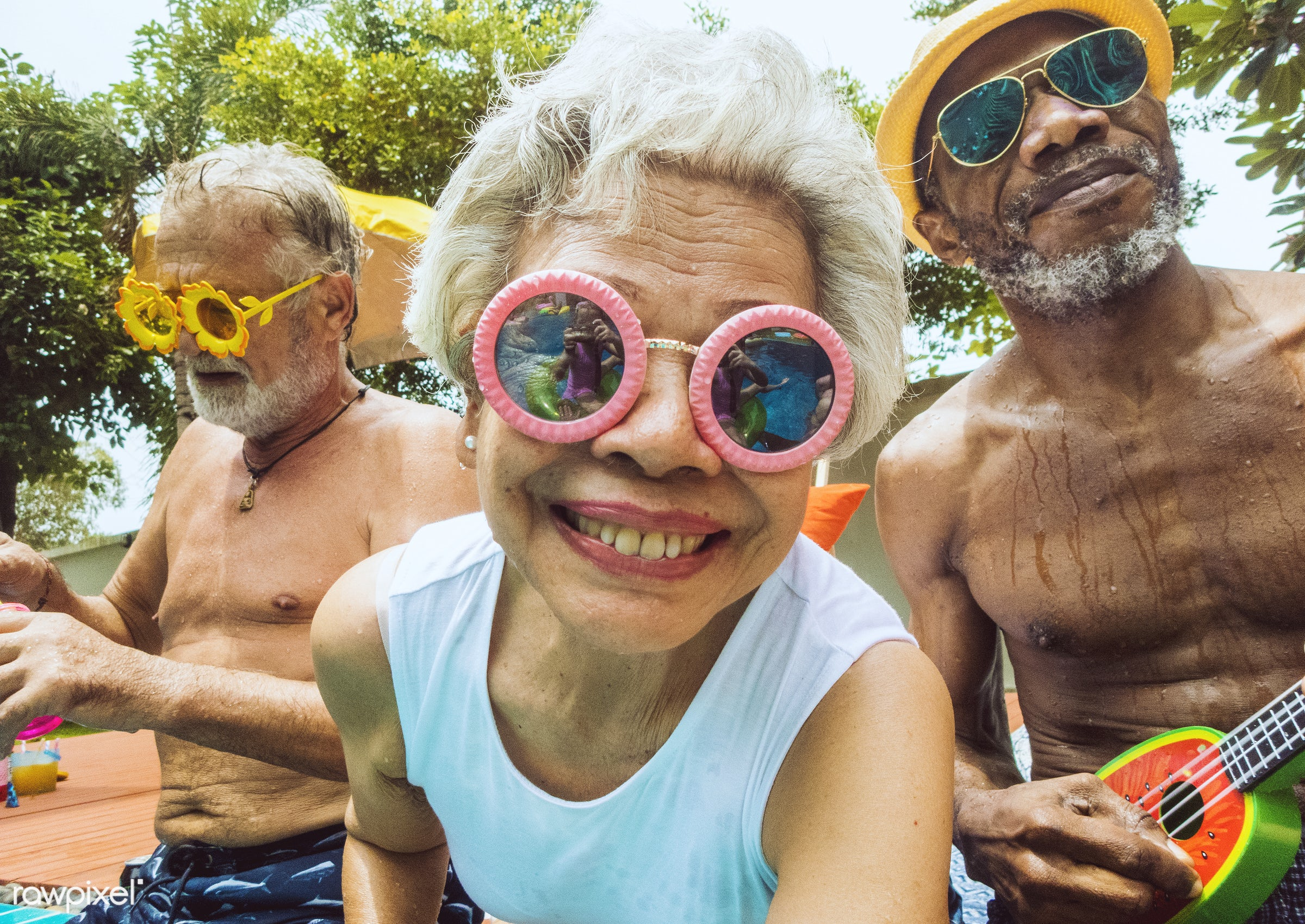 Closeup of diverse senior adults sitting by the pool enjoying summer together - senior, happy, fun, party, family, summer,...