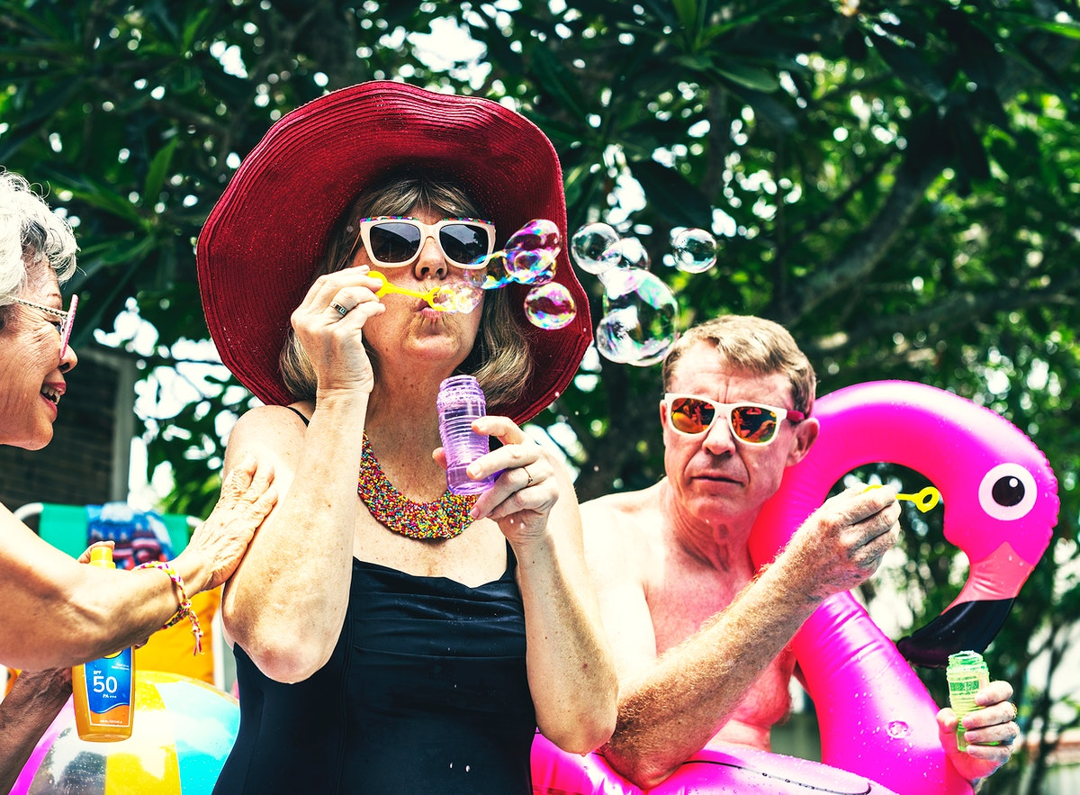 Group of diverse senior adults sitting at poolside blowing soap bubbles