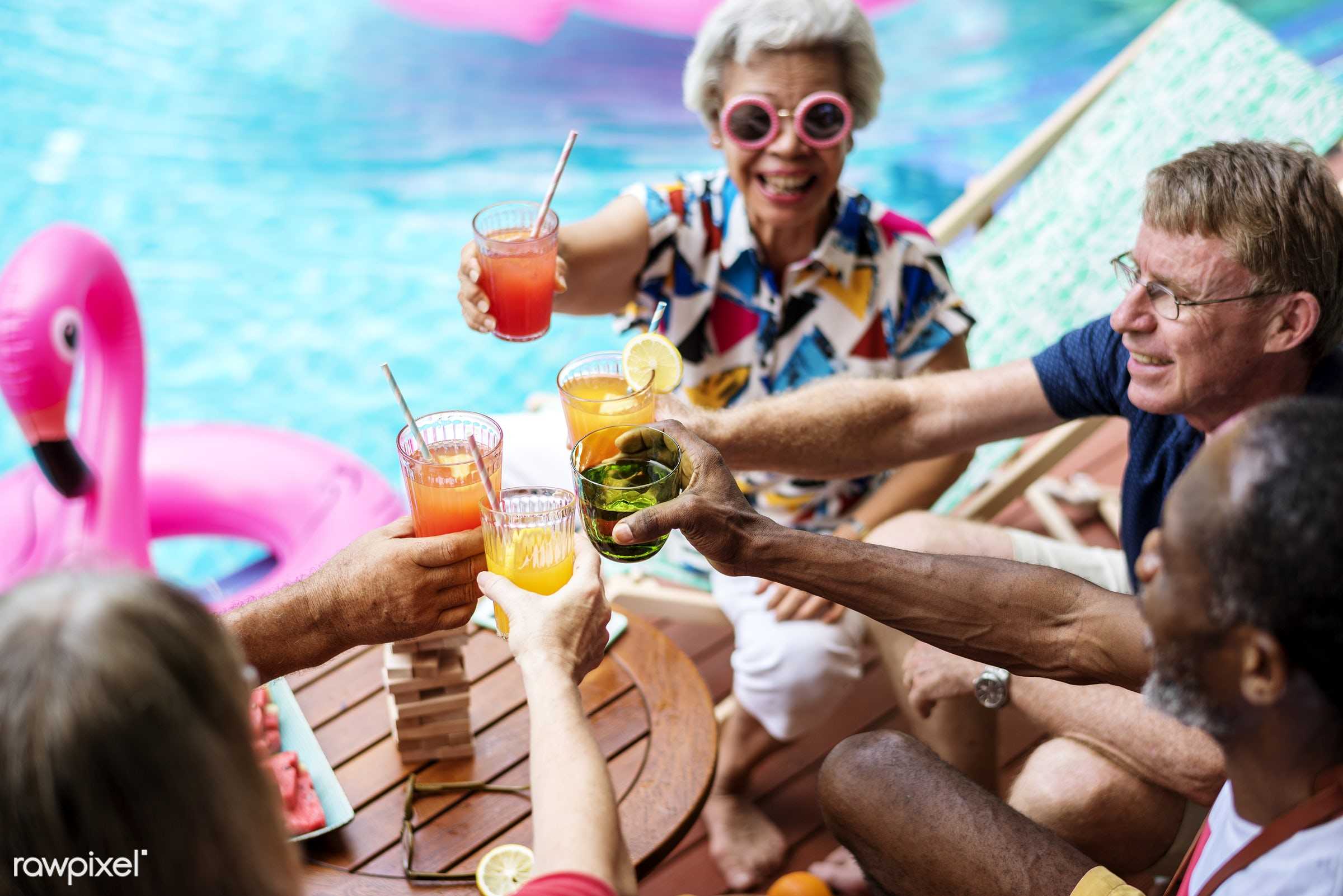 Group of diverse senior adult enjoying beverage by the pool together - tube, diverse, relax, swimming pool, party,...