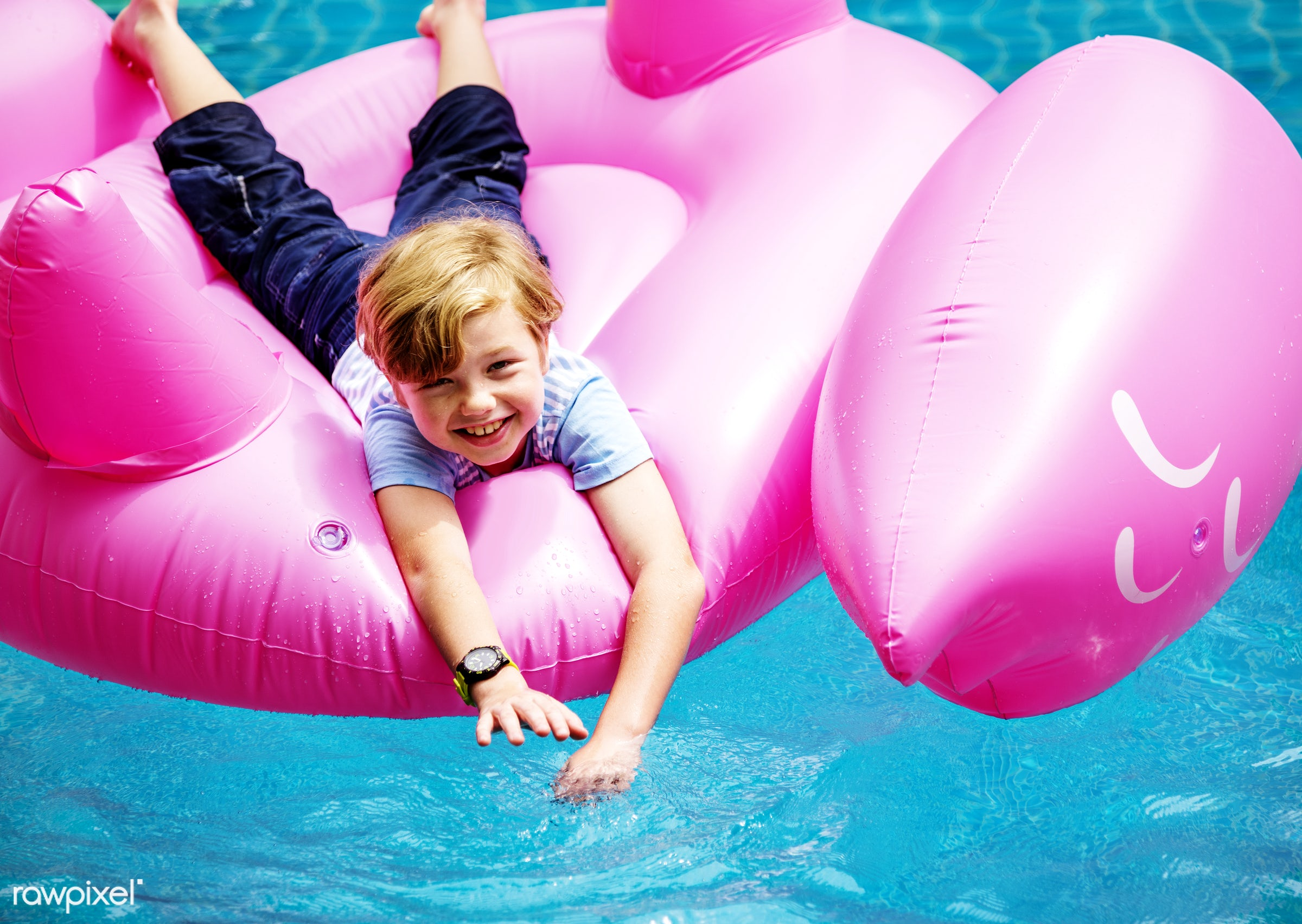 Aerial view of young caucasain boy floating in the pool with flamingo shape inflatable tube - aerial view, alone, boy,...